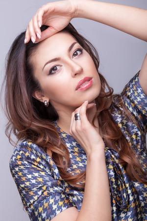 Mooie brunette model op een grijze achtergrond met haar hand boven het hoofd. Professionele make-up en studio verlichting