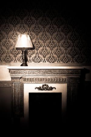 Mooie oude lamp op de open haard in rode vintage kamer
