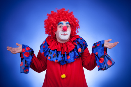 Surprised clown on blue background. Studio professional lighting