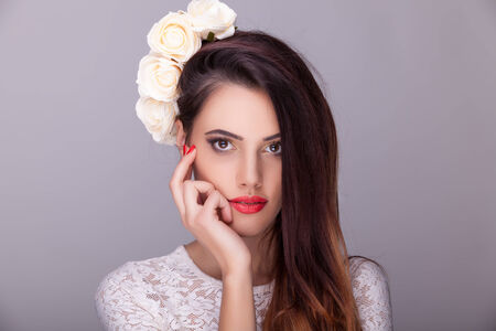 Beautiful woman flowers in head on grey background. Professional make up and hairstyle. Studio lighting