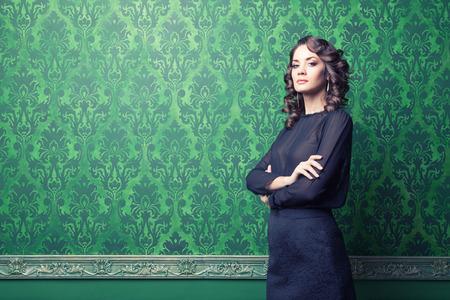 Sensual woman in green vintage interior Stock Photo