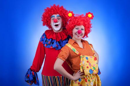 Clown paar in kostuums op een blauwe achtergrond. Studio professionele verlichting. Levendige kleuren