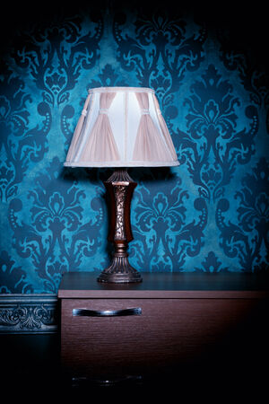 Retro lamp on blue rococo background. Vintage pattern. Vintage lamp. Vignette. Rich rustic interior