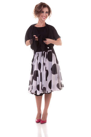 Woman in dress with dots isolated on white background. Professional studio lighting. Full body photo