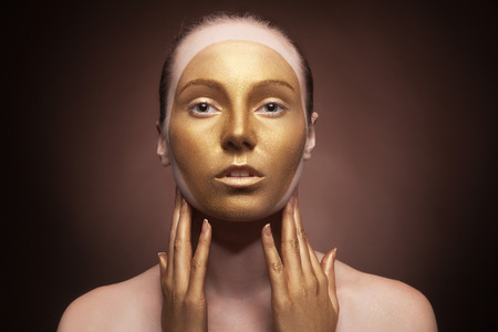 Woman with fashion art make up on brown background. Professional studio lighting. Fashion art style. Close up portrait
