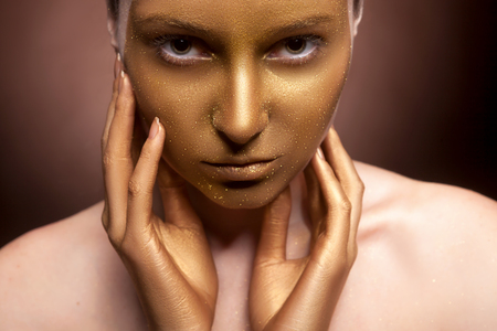 fashion make up: Woman with art fashion make up on face. Brown background. Gold skin type make up Stock Photo