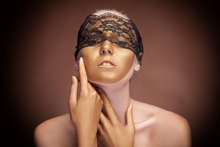 Woman with face in gold paint and lace over face. Sensuality. Brown background. Vignette photo