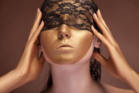 Woman with a gold fashion face and lace on her eyes. Professional make up. Sensuality. Gold oil. Mouth photo