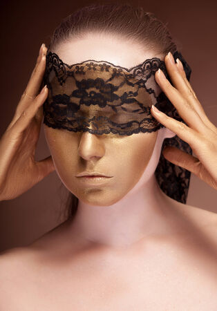 Sensual woman with a lace on her face. Gold skin make up. Fashion gold make up photo