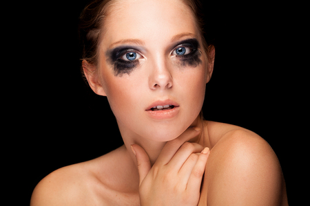 Beautiful girl with fashion crying make up and blue eyes isolated on black background. Fashion, glamour and high end retouching. Perfect skin with texture. Blue eyes. Cosmetics and make up photo