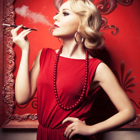 Beautiful sensual blonde smoking a cigarette in red vintage room. Professional make up and hairstyle. Retro and vintage. Toned image. photo