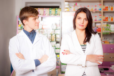 Druggist and client in front of pharmacy table. Drugs and pills in the background. Medical background photo