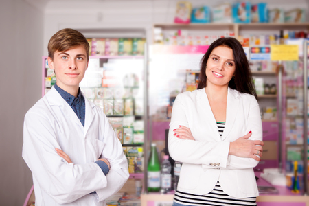Customer and pharmacist smiling on drugs and pills background. Shot real pharmacy. Young pharmacist and average client photo