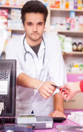 giving back: Smiling doctor giving back credit card to customer in a pharmacy. Healthcare and customer care. Medical background. Young smiling pharmacist