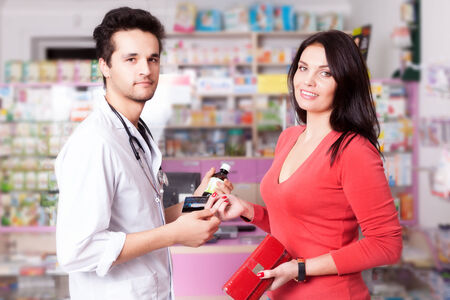 custumer: Pharmacist with client inside pharmacy. Custumer care. Healtcare. Medical business. Business style Stock Photo