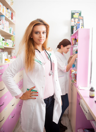 custumer: Smiling pharmacist in front and the second one looking in the back for some products. Pharmacy lifestyle. Healthcare business. Custumer care Stock Photo