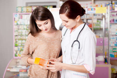 custumer: Pharmacist woman showing product to custumer interior of real pharmacy. Customer care. Healthcare business