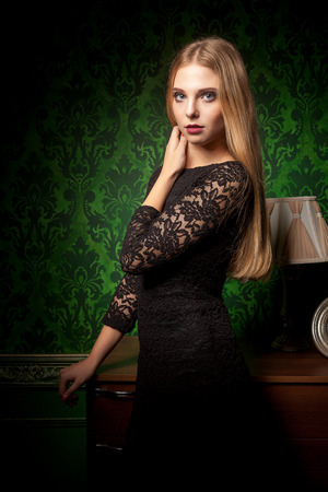 Sexy woman in black dress in green retro interior. A lamp is on the shell behind. Beauty and sensuality. Fashion and old-styled
