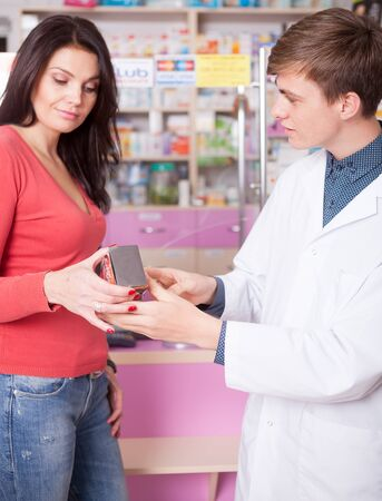 Male pharmacist showing product to client insisde pharmacy. Healthcare business. Healthcare and clientcare Stock Photo