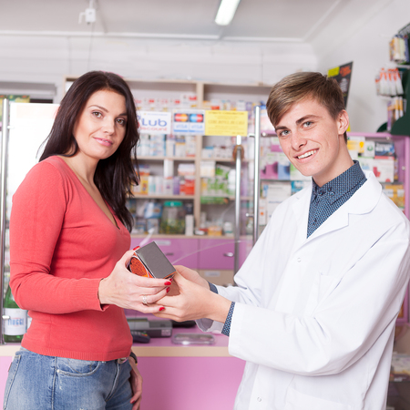 Smiling doctor and client inside pharmacy with product in hands looking to the camera. Healthcare business. Medical business. Medicine