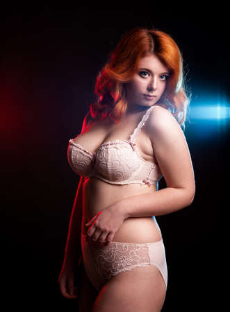 Chubby woman in underwear on black background. Studio shooting. Overweight redhead model. Sexy woman with big boobs
