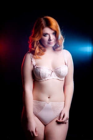 redhead lingerie: Chubby woman in underwear on black background with two light behind her. Over weight model Stock Photo
