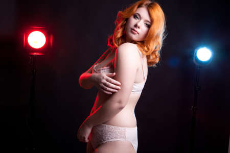 chubby girl: Chubby girl in underwear with two lights behind on black background. Studio shooting. Doll look a like girl