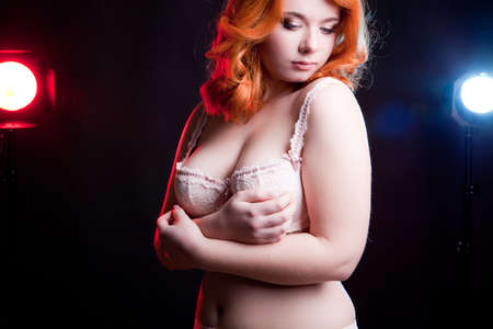 Sexy overweight woman in studio on black background with two light behind her. Chubby but sexy woman Stock Photo