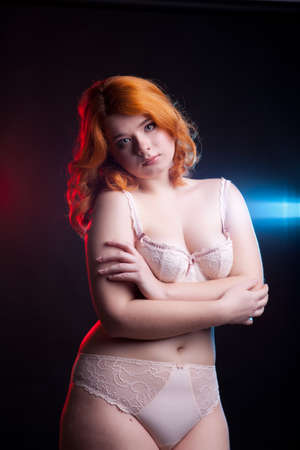 to size: Sexy overweight woman in studio on black background with two light behind her. Chubby but sexy woman Stock Photo