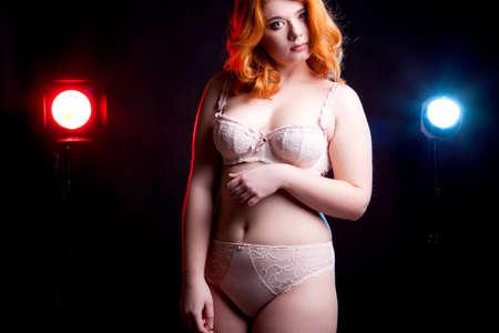 mujer celulitis: Niñas con sobrepeso en lijerie sobre fondo negro con dos luces detrás de ella. Shooting del estudio Foto de archivo