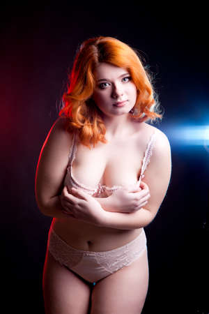 overweight girl: Overweight girl in lijerie on black background with two lights behind her. Studio shooting