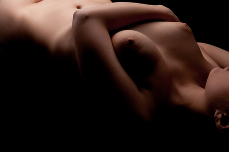 Nude female body with big tits on black background. Studio artistic shooting. Sexuality and sensuality. Beauty and boudoir. Stock Photo