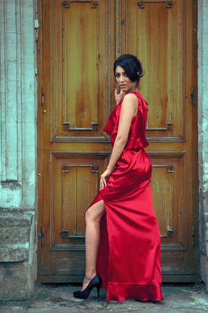 outside shooting: Sexy woman in red dress in front of door. Outside fashion shooting. Red dress. Beautiful girl in sensual red dress.
