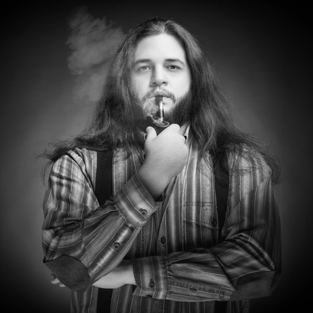 professional lighting: Men with long hairs smoking pipe. Studio professional lighting. Concept. Beauty. Fashion