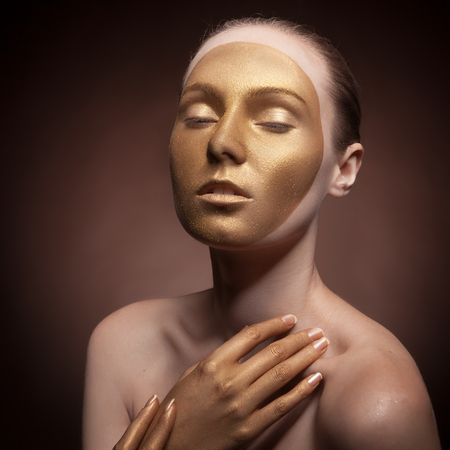 stage make up: Beautiful woman with art fashion make up. Cosmetics and art fashion. Gold tone. Studio lighting. Face painting Stock Photo
