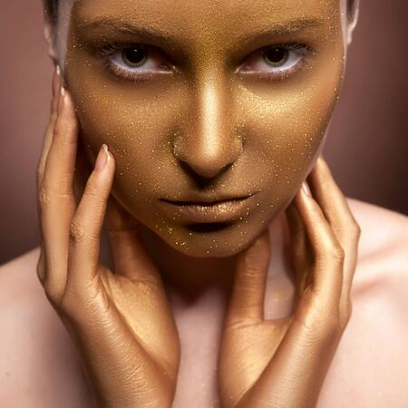 ceremonial make up: Woman with art fashion make up on face. Brown background. Gold skin type make up Stock Photo