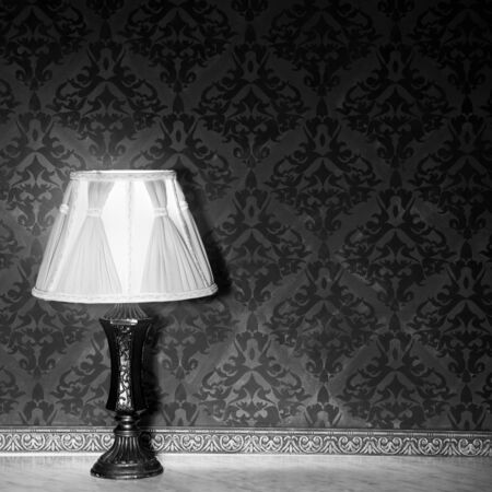 professional lighting: Vintage lamp on a retro fireplace. Toned image. Red vintage pattern. Studio professional lighting