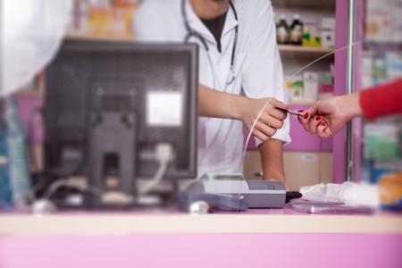 farmacia: Cliente está pagando con tarjeta de crédito para pastillas en la farmacia. Negocio de la salud. Realations negocio. Farmacia
