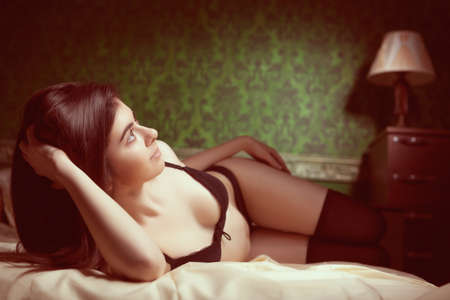 mujeres desnudas: Muchacha en ropa interior negro en la cama en muy rico interior verde con el patrón de la vendimia. Tonificación retro de la imagen. Boudoir photoshooting con la muchacha atractiva