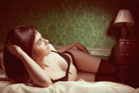 seni: Ragazza in biancheria nera a letto in verde, molto ricco interno con modello d'epoca. Retro tonificazione dell'immagine. Boudoir photoshooting con la ragazza sexy Archivio Fotografico