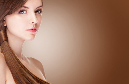 mujer maquillandose: Chica con la piel perfecta sobre fondo marrón. Shooting del estudio. Maquillaje y belleza. Moda y glamour. Peinado perfecto y piel saludable
