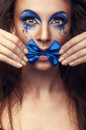 extravagant: Woman with fashion make up and bow in mouth. Studio shooting. Beauty and fashion. Extravagant make up with style concept. Blue make up Stock Photo