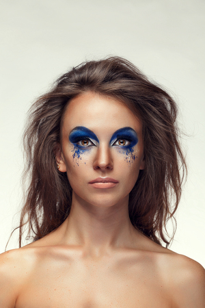 Girl with fashion extravagant blue make up. Studio shooting over grey background. Art fashion make up Stock Photo