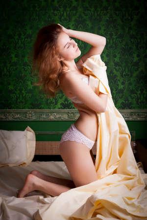 femme sexe: Jeune fille rousse sexy en lingerie blanche sur fond vert cru posant sexuelle � la cam�ra