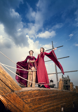 contrasty: Two elegant woman in extravagant antique luxury clothes on boat deck with a very contrasty sky