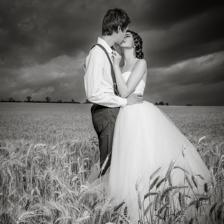 married couples: Young married couple in wheat field with beautiful blue sky. Brige and groom. Young happy family. Love and emotions. black and white