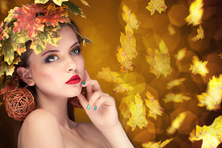 hair style: Autumn fashion concept of girl with leafs in head. Studio shooting. Beauty and fashion. Season concept. Autumn portrait with yellow leaves hair style. Beauty fashion art model girl with autumnal make up and Hairstyle. Creative Autumn Makeup.