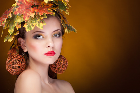 Sensual woman with leafs in head. Autumn portrait with yellow leaves hair style.  Fall. Autumn woman Portrait. Beauty fashion art model girl with autumnal make up and Hairstyle. Creative Autumn Makeup. Beautiful Face