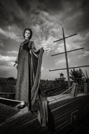 aristocracy: Woman in aristocratic clothes on boat in retro vintage concept. Elegancy and aristocracy. Rich woman from medieval period. Black and white image