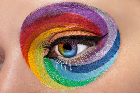 stage make up: Close up eye with artistic rainbow make up. Colors and colorful. Joy. Artistic and fashion make up. Make up addiction. Cosmetics. On stage make up